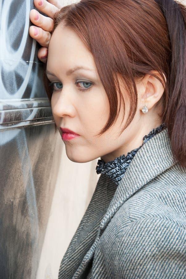 Traurige junge Frau steht nahe Wand lizenzfreie stockfotografie