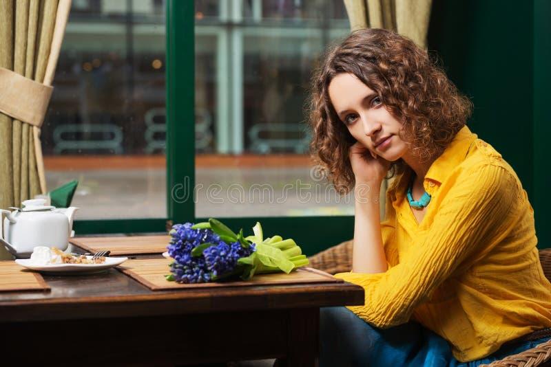 Traurige junge Modefrau im gelben Hemd am Restaurant lizenzfreie stockbilder