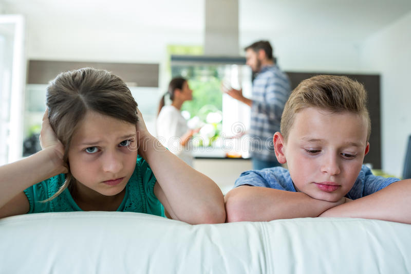 Traurige Kinder, die auf Sofa während Eltern argumentieren im Hintergrund sich lehnen stockbild