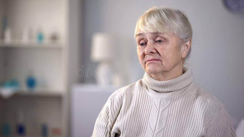 Traurige ?ltere Frau, die allein im Wohnzimmer, denkend an Gesundheitsprobleme sitzt stockfoto