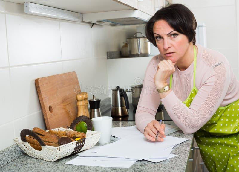 Traurige Mitte gealterte Hausfrau, die durch Rechnungen schaut lizenzfreies stockfoto