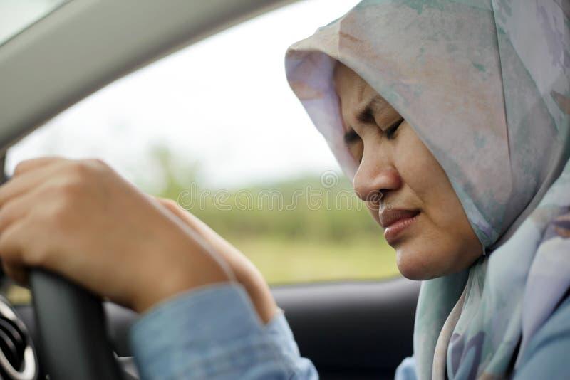 Traurige moslemische Dame Driving Her Car und Schreien stockfotos