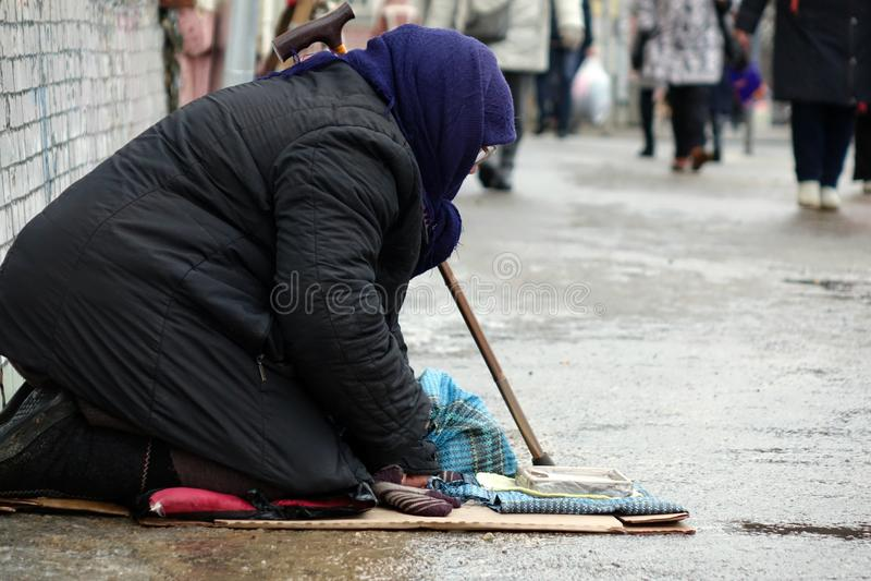 Traurige obdachlose Frau, die auf der Obdachlosen vorbei überschreitet sitzt lizenzfreies stockbild