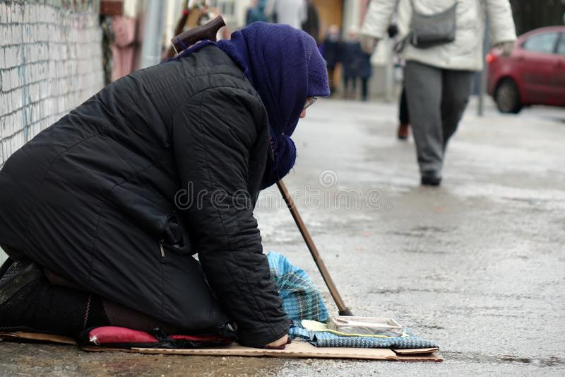 Traurige obdachlose Frau, die auf der Obdachlosen vorbei überschreitet sitzt stockfotografie
