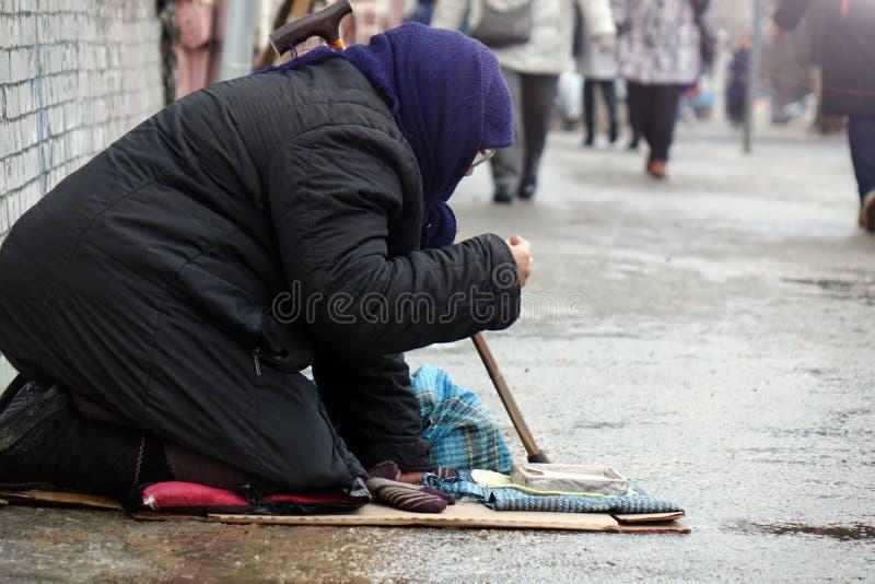 Traurige obdachlose Frau, die auf der Obdachlosen vorbei überschreitet sitzt lizenzfreie stockfotos