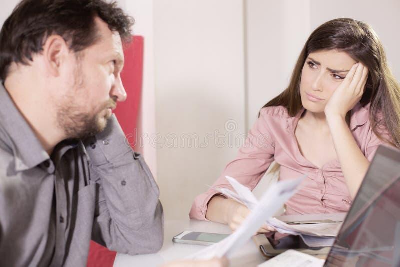 Traurige Paare, die einander unglücklich über Rechnungen betrachten stockbilder