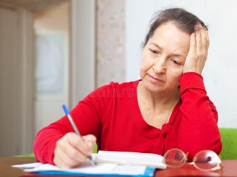 Traurige reife Frau mit Stromrechnungen stockbild