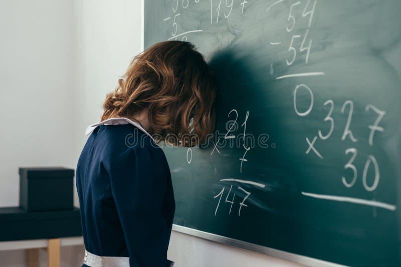 Traurige Schülerin, die versucht, ein Beispiel zu lösen Schulmädchen steht mit ihrer Stirn auf der Tafel lizenzfreies stockbild
