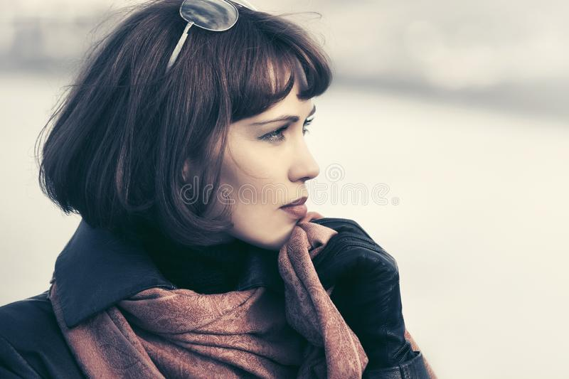 Traurige sch?ne Modefrau im Ledermantel im Freien stockfoto