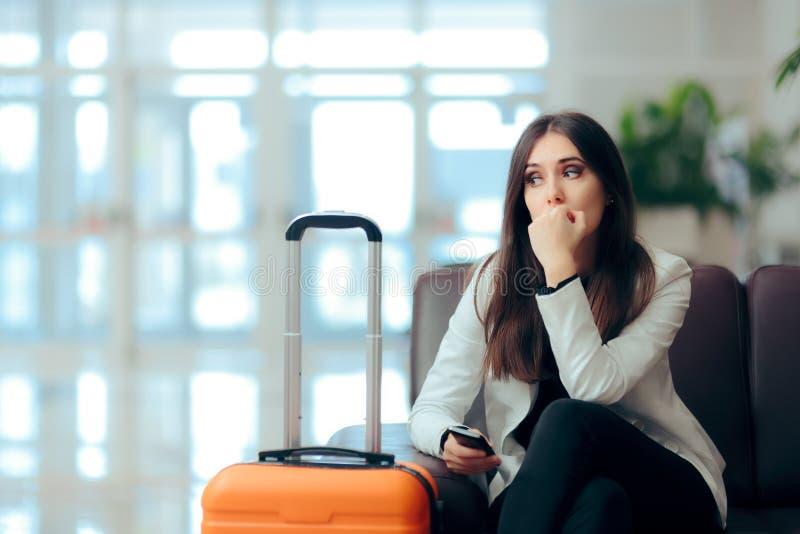 Traurige schwermütige Frau mit Koffer im Flughafen-Warteraum lizenzfreie stockfotografie