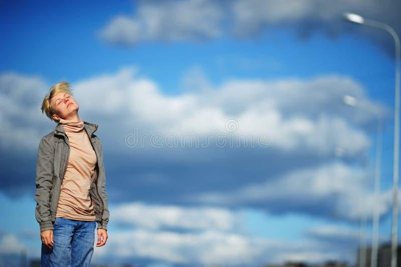 Traurige und betonte leidende Migränekopfschmerzen der jungen Frau des Porträts, blauer Himmel und Wolken als Hintergrund stockbilder