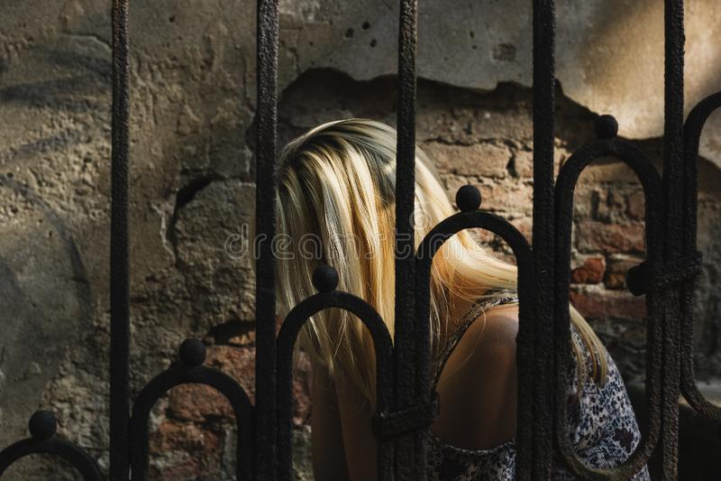 Traurige und einsame blonde behaarte Frau, die hinter dem Eisenzaun sitzt lizenzfreie stockfotografie