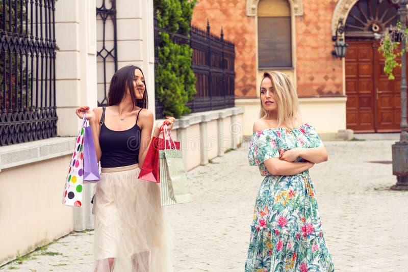 Traurige und glückliche Frau, die am Einkaufen argumentiert stockbilder