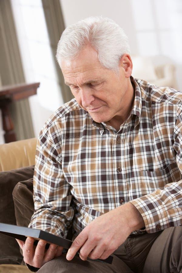 Trauriger älterer Mann, der Fotographie betrachtet stockbilder