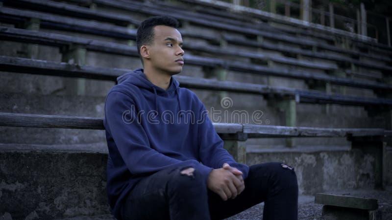 Trauriger Afroamerikanerjugendlicher, der herum auf Tribüne, Verwüstung und Armut sitzt lizenzfreies stockfoto