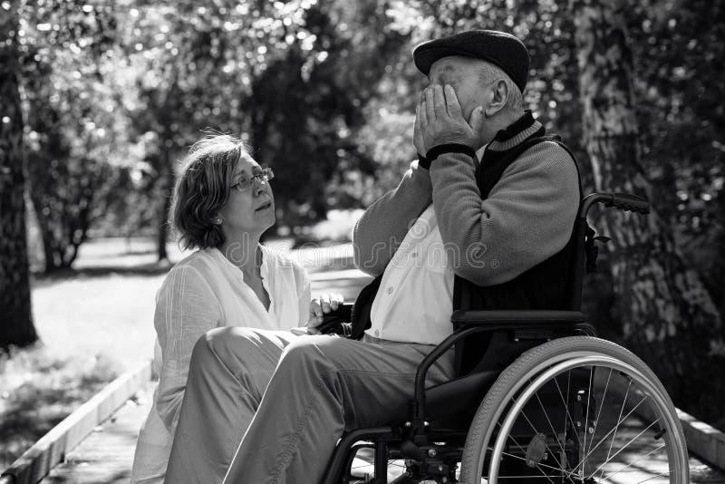 Trauriger alter Mann auf Rollstuhl und junger Frau im Park lizenzfreies stockfoto