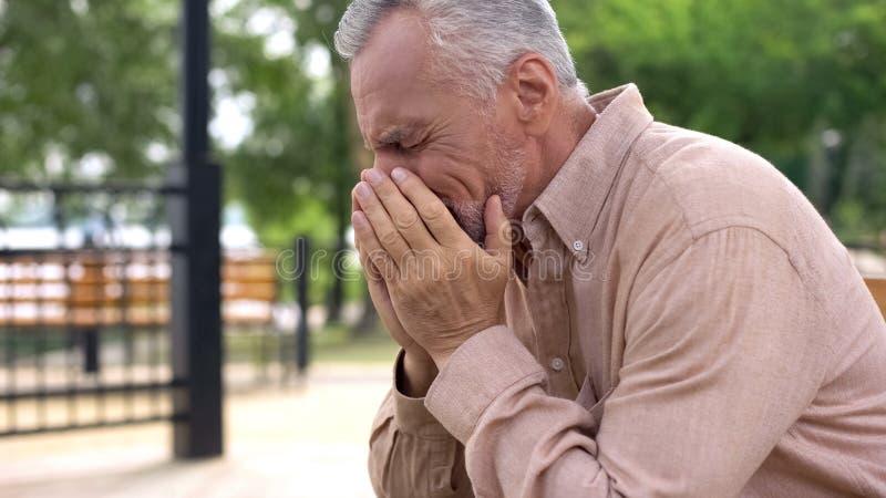 Trauriger alter Mann, der auf Krankenhausgartenbank, Pensionär schreit in der Sorge, Verlust sitzt stockfotografie