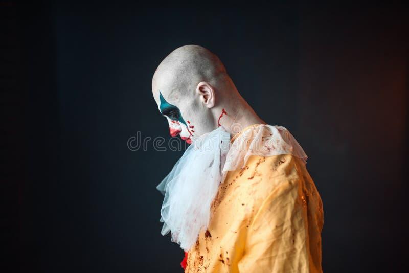Trauriger blutiger Clown mit Make-up im Karnevalskostüm stockfotos