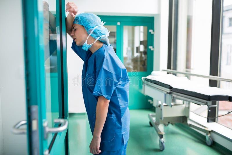Trauriger Chirurg, der an der Glastür sich lehnt lizenzfreies stockbild