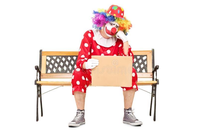 Trauriger Clown, der auf Bank sitzt und ein Zeichen hält lizenzfreies stockfoto