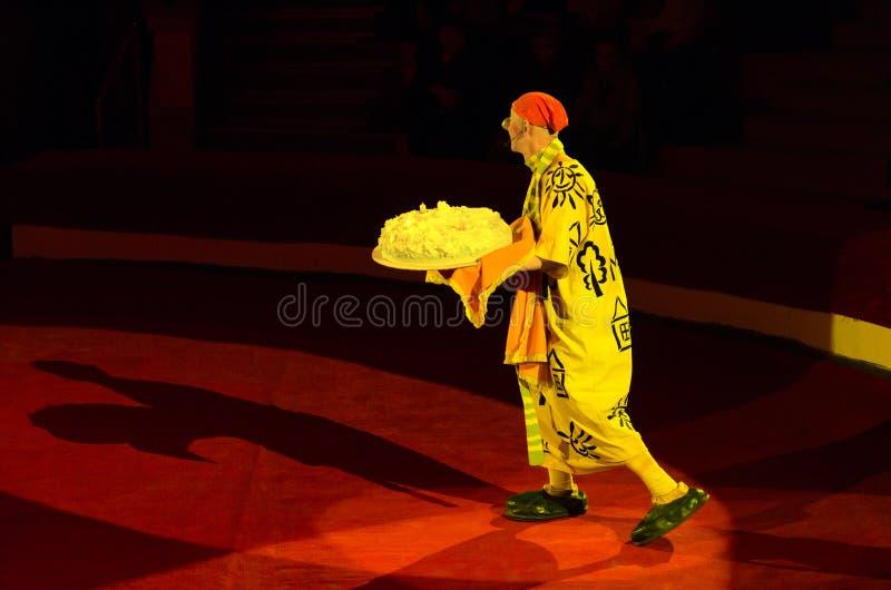 Trauriger Clown geht zur Arena mit großem Feiertagskuchen in seinen Händen stockfoto