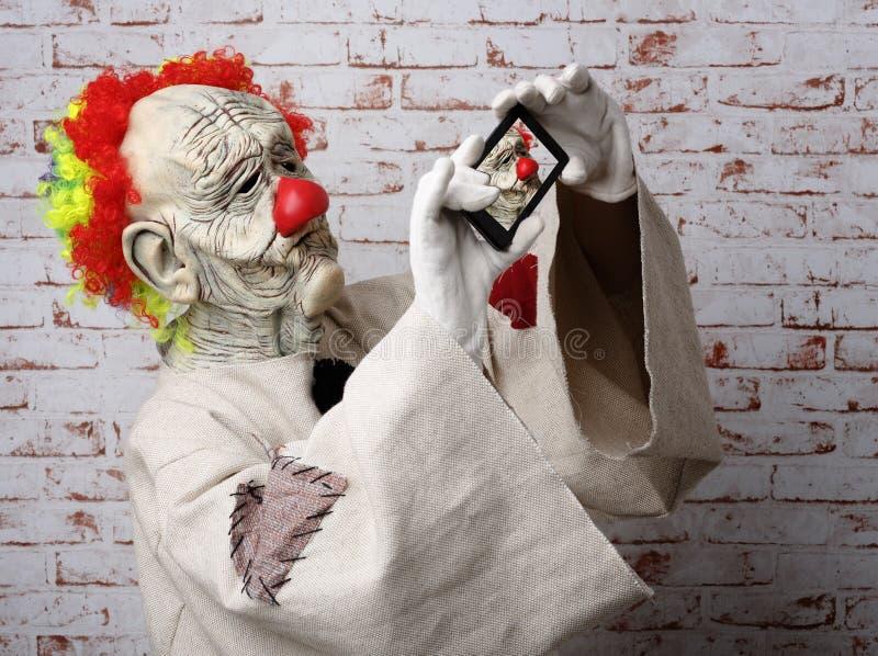 Trauriger Clown macht selfie auf Mobiltelefon stockbild