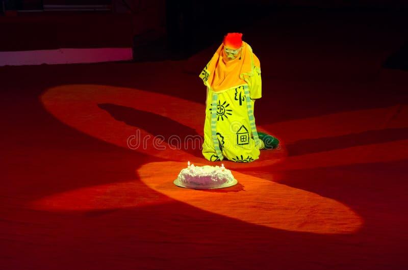 Trauriger Clown sitzt auf Arena nahe großem Geburtstagskuchen mit brennenden Kerzen und betrachtet ihn stockbild