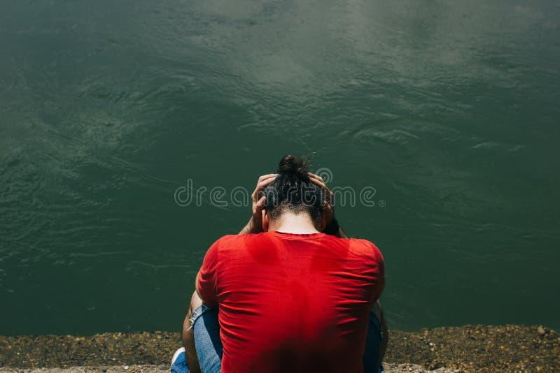 Trauriger, deprimierter Mann in sitzender Bucht des roten Hemdes das düstere grüne Wasser stockfotos