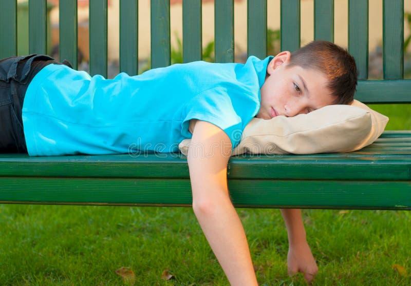 Trauriger einsamer Teenager, der auf der Bank liegt stockfotos