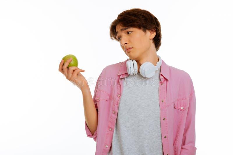 Trauriger freudloser Junge, der den Apfel betrachtet lizenzfreie stockbilder
