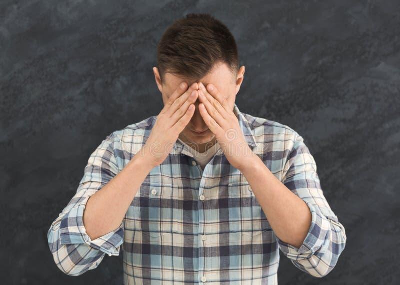 Trauriger freudloser Mann, der sein Gesicht bedeckt lizenzfreie stockbilder