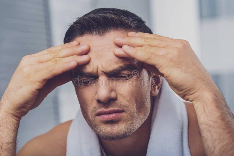 Trauriger freudloser Mann, der seine Stirn hält lizenzfreie stockfotografie