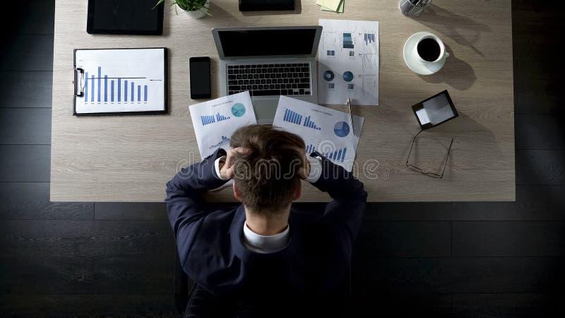 Trauriger Geschäftsmann, der bei Tisch sitzt und an Schulden, Konkurs, Draufsicht denkt lizenzfreies stockbild