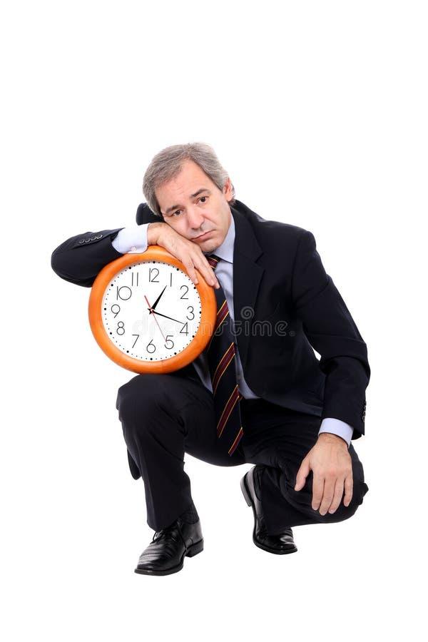 Trauriger Geschäftsmann, der eine Borduhr anhält stockfotos