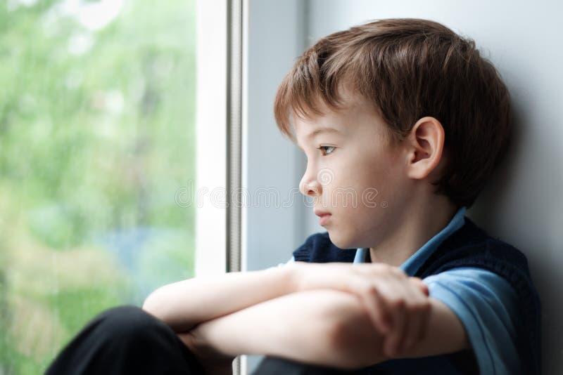 Trauriger Junge, der auf Fenster sitzt lizenzfreies stockbild