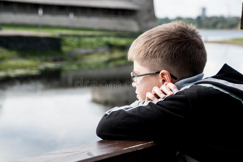 Trauriger Junge, der den Fluss betrachtet stockfotos