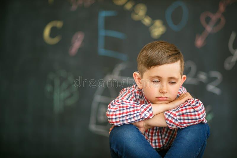Trauriger Junge, der mit geschlossenen Augen vor dem hintergrund der Schulbehörde sitzt lizenzfreies stockfoto