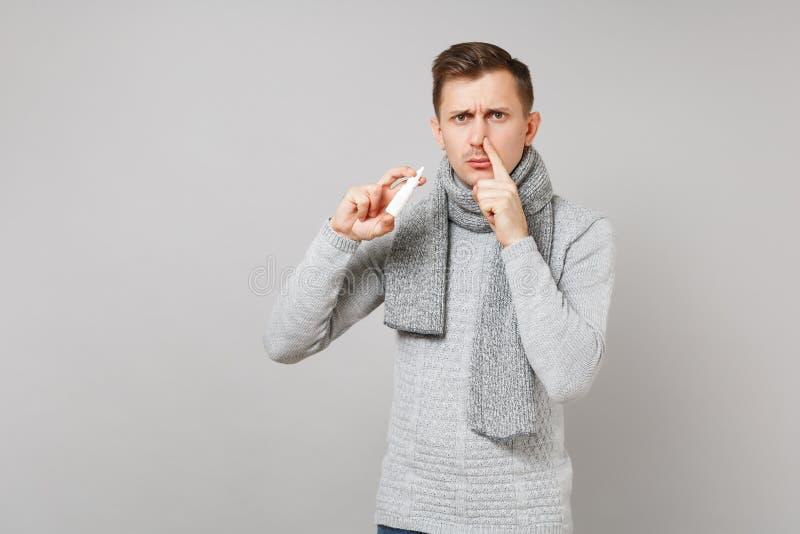 Trauriger junger Mann in der grauen Strickjacke, Schal, der die nasalen Tropfen bedecken Nasenloch mit dem Finger auf grauem Hint lizenzfreies stockfoto