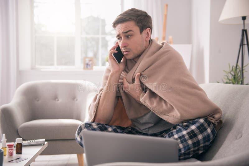 Trauriger junger Mann, der mit seinem Arbeitgeber spricht lizenzfreie stockfotos