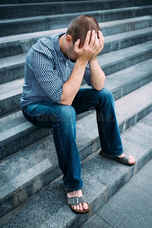 Trauriger junger Mann, der sein Gesicht mit den Händen sitzen auf Treppe bedeckt lizenzfreie stockfotografie