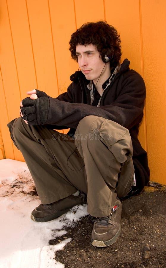 Trauriger junger Mann mit Haupttelefonen lizenzfreie stockfotos