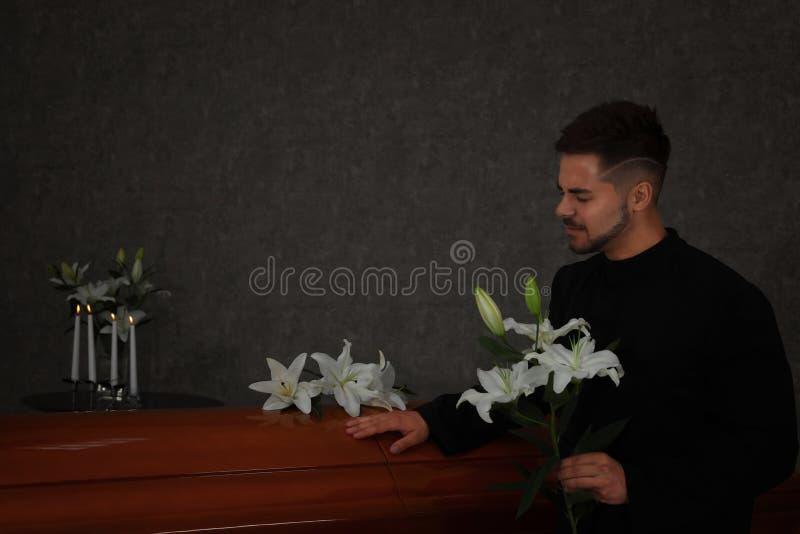 Trauriger junger Mann mit Lilien nahe Schatulle im Beerdigungsinstitut lizenzfreie stockfotografie
