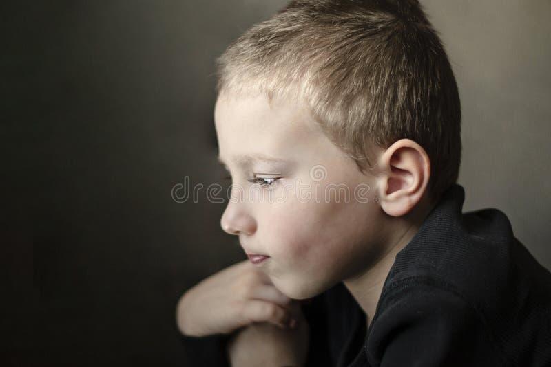 Trauriger junger unten schauender und denkender Vorschule- Junge Unglückliches Kind mit traurigem Gesicht auf dunklem Hintergrund stockfotos