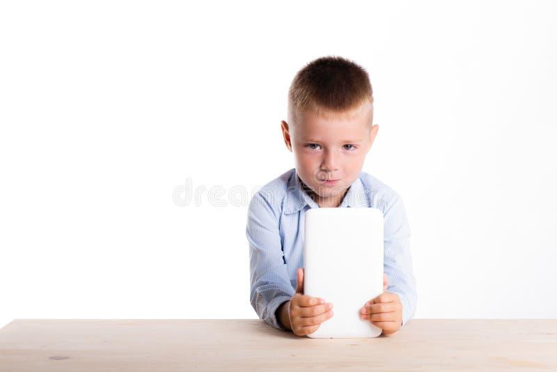 Trauriger kleiner Junge in der Klage, die bei Tisch mit Tablettengerät sitzt Chil lizenzfreies stockbild