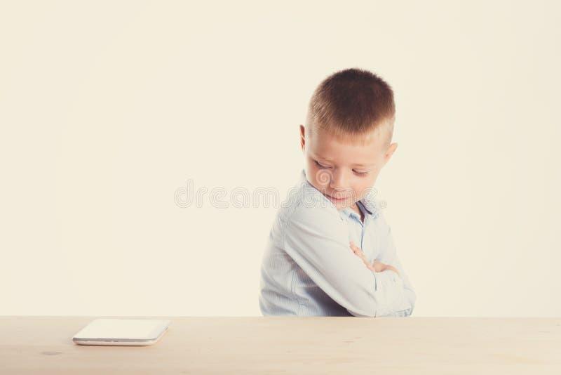 Trauriger kleiner Junge in der Klage, die bei Tisch mit Tablettengerät sitzt Ein Portrait des Mädchenabschlusses oben Zurück zu S stockbild