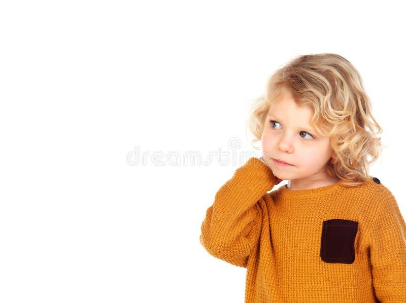 Trauriger kleiner Junge, der seinen Kopf verkratzt lizenzfreie stockfotos