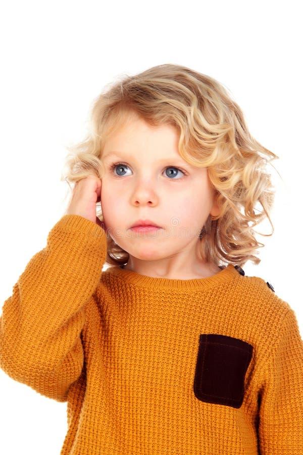 Trauriger kleiner Junge, der seinen Kopf verkratzt lizenzfreie stockbilder