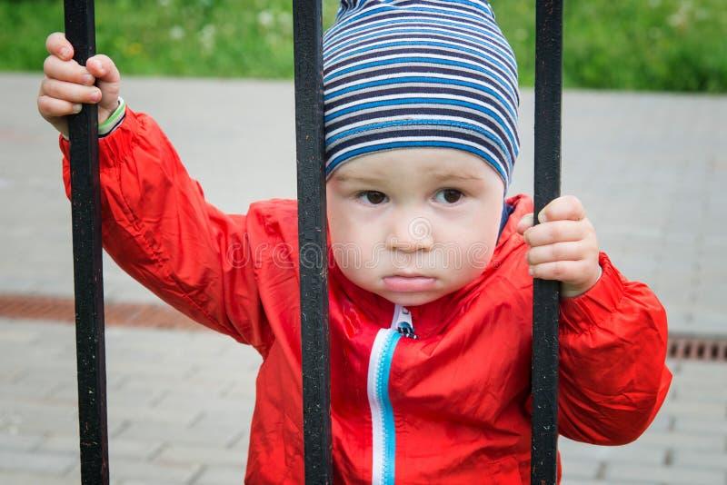 Trauriger kleiner Junge schaut durch ein Gitter stockbild
