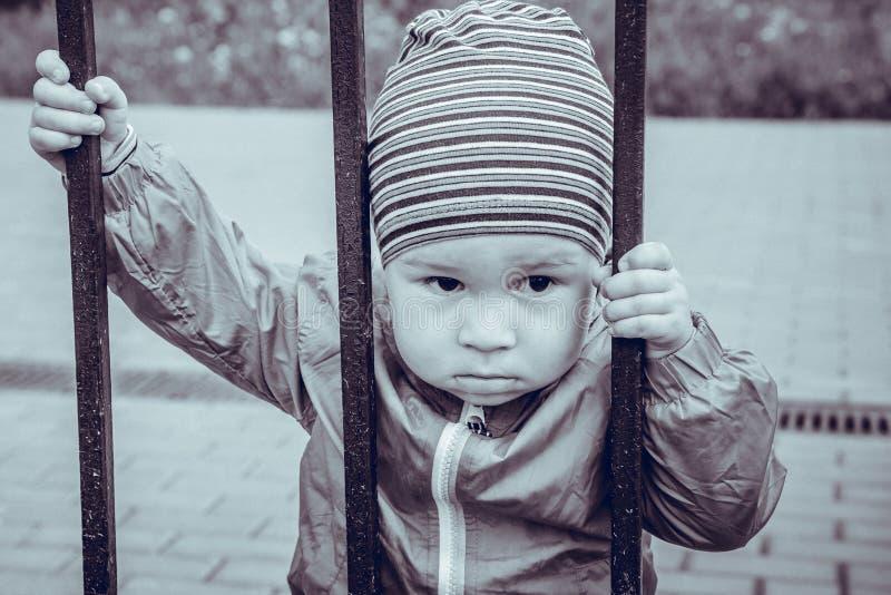 Trauriger kleiner Junge schaut durch ein Gitter stockfoto