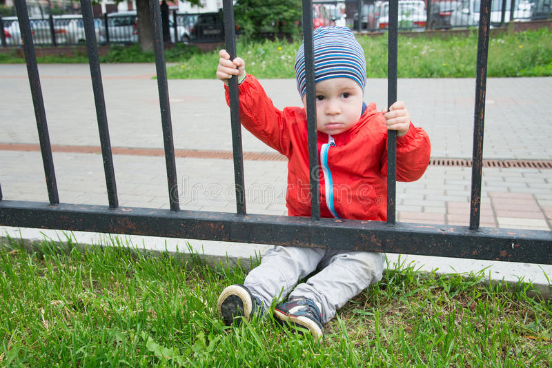 Trauriger kleiner Junge schaut durch ein Gitter stockfotografie